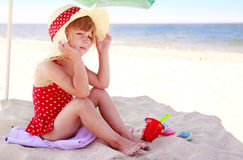 Little girl playing on the sea shore Stock Photos