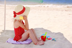 Little girl playing on the sea shore Stock Images