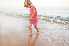 Little girl playing on the sea shore Stock Photo