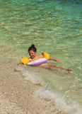 Little girl playing in sea waves. Plaka beach, Pelion, Greece Royalty Free Stock Photo