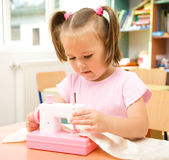 Little girl is playing with sewing machine Stock Photos