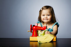 Little girl is playing with sewing machine Royalty Free Stock Photography