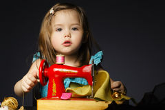Little girl is playing with sewing machine Royalty Free Stock Photos