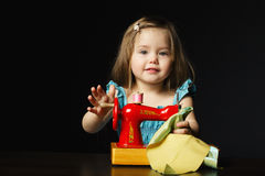 Little girl is playing with sewing machine Royalty Free Stock Images