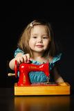 Little girl is playing with sewing machine Stock Photo