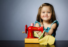 Little girl is playing with sewing machine Stock Images