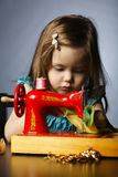 Little girl is playing with sewing machine Stock Photography