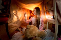 Little girl playing in shadow theater in bedroom at night Royalty Free Stock Image