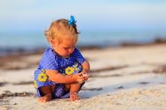 Little girl playing with shells on the beach Royalty Free Stock Photos