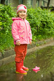 Little girl playing with ship in the puddle Royalty Free Stock Photos