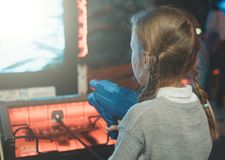 Little girl playing shooter game. Royalty Free Stock Image
