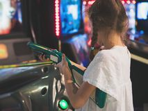Little girl playing shooter game. Stock Photo