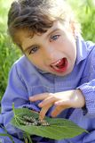Little girl playing with silkworm in hands Stock Photo