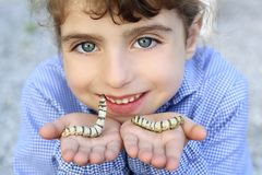 Little girl playing with silkworm in hands. With school uniform and smiling Stock Photography