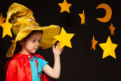 Little girl playing sky watcher with handmade star. Beautiful five years old girl playing sky watcher with handmade stars and moon against black background Royalty Free Stock Photography