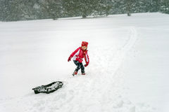 Little girl playing with sled in  snow while snowflurry Royalty Free Stock Photos