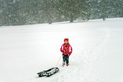 Little girl playing with sled in  snow while snowflurry Royalty Free Stock Images