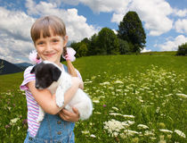 Little girl playing with small  puppiy Stock Images