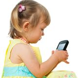 Little girl playing with smartphone. Royalty Free Stock Images