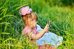 Little girl  playing with a smartphone. Cute little girl sitting In grass playing with a smartphone Stock Photos