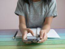 A little girl playing smartphone with doing homework on the colourful table royalty free stock image
