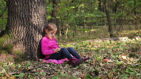 Little girl playing on a smartphone in the forest, sitting under a tree stock footage
