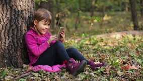Little girl playing on a smartphone in the forest, sitting under a tree stock video footage