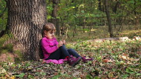 Little girl playing on a smartphone in the forest, sitting under a tree stock video