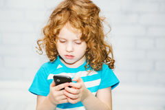 Little girl playing on a smartphone on a light background. Stock Images