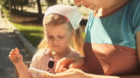 Little girl is playing on a smartphone lying in the hands of her mom outdoors. Little girl playing in the app by clicking on the screen of the smartphone, which
