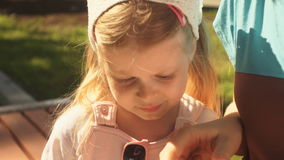 Little girl is playing on a smartphone lying in the hands of her mom outdoors