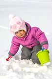 Little girl playing with snow. Spade and pail Royalty Free Stock Image