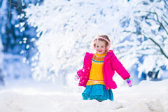 Little girl playing snow ball fight in winter park Royalty Free Stock Photos