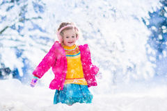 Little girl playing snow ball fight in winter park. Funny little toddler girl playing snow ball fight. Kids play outdoors in winter. Children having fun at  time Royalty Free Stock Photography