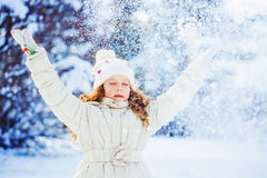 Little girl playing with snow. Falling snow around the child. Ha Royalty Free Stock Photography