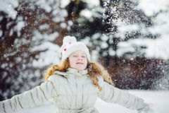 Little girl playing with snow. Falling snow around the child. Royalty Free Stock Images