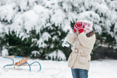 Little girl playing in the snow and throw snowballs Royalty Free Stock Photography