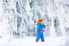 Little girl playing with snow in winter Stock Images