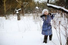 Little girl playing snowballs Stock Photography