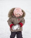 Little girl playing with snowballs Royalty Free Stock Photo