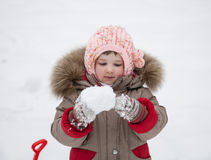 Little girl playing with snowballs stock photos