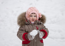 Little girl playing with snowballs Stock Photo