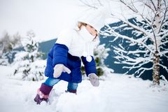 Little girl playing snowballs, winter activity. Royalty Free Stock Photos