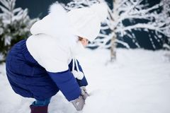 Little girl playing snowballs, winter activity. Stock Photos