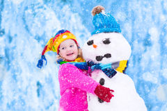 Little girl playing with a snowman Stock Photo