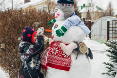 Little girl playing with snowman royalty free stock images