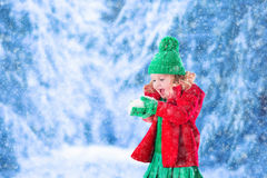 Little girl playing in snowy park Royalty Free Stock Image