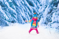 Little girl playing in snowy winter forest Royalty Free Stock Photo