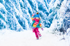 Little girl playing in snowy winter forest Royalty Free Stock Photos