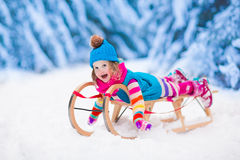 Little girl playing in snowy winter forest Royalty Free Stock Image